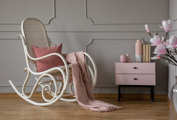 Pink blanket on rocking chair in grey living room interior with flowers and cabinet. Real photo