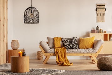Obraz Scandinavian sofa with pillows and dark yellow blanket in bright living room interior with black chandelier - fototapety do salonu