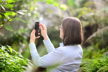 A woman takes selfie with smartphone in a glass botanical garden with tropical plants. A tropical climate in the middle of winter in the city. Playful, funny, happy, blur, clean, bright, horizontal.
