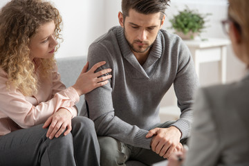 Beautiful wife supporting her husband during psychotherapy session with counselor