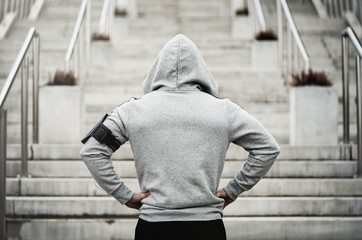 Rear view of hooded sports man about to run upstairs
