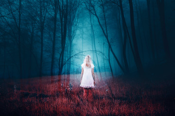 Woman standing in foggy mysterious fantasy forest with grass on the floor. The image with the effect of double exposure. Wall mural