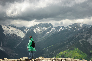 male traveller on the top of mountain stormy landscape