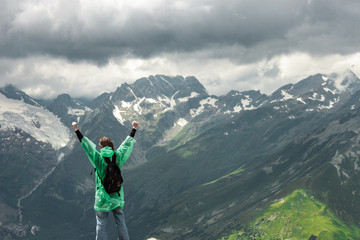 happy traveller on the top of mountain stormy landscape