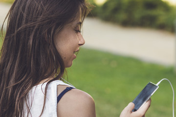 close-up portrait of young woman listening to the music on the phone