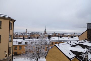 View over snowy rooftops with Riddarholmen behind, Stockholm Sweden