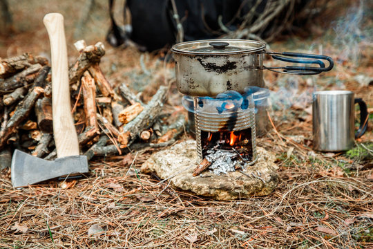 axe near a firewoods, camping diy woodstove, camping utensils and backpack on the background