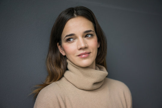 Portrait of smiling woman wearing light brown turtleneck pullover against grey background