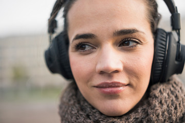 Portrait of smiling woman wearing scarf listening music with cordless headphones, close-up