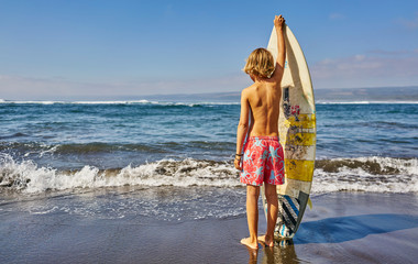 Chile, Pichilemu, boy standing at the sea with surfboard