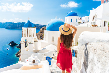 Luxury travel vacation Europe holiday Santorini girl in hat and red fashion dress walking 3 blue domes famous tourist attraction. Summer sun holidays adventure. Fotomurales