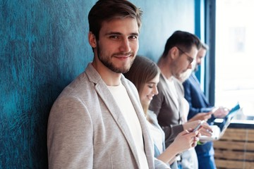 The connected team is an efficient team. Group of businesspeople using wireless technology together while standing in line against a blue background.