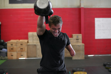 Aggressive male adaptive athlete lifting kettlebell while standing against wall in gym