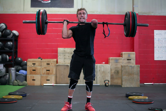 Confident male adaptive athlete lifting barbell while standing against wall in gym