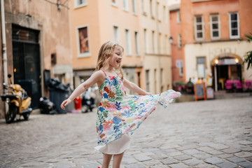 Happy cute girl wearing dress spinning on street against buildings in city