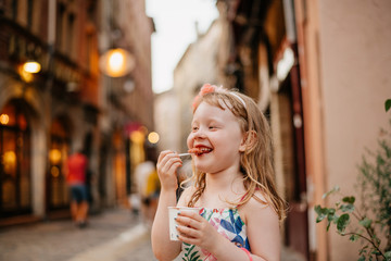 Happy girl eating food while standing on street against buildings in city