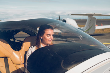 Confident female pilot sitting in airplane seen through windshield at airport during sunny day