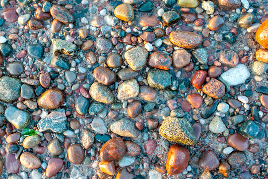 surface of small colorful wet stones, background, texture