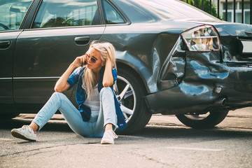 girl sits on the road, near the broken car and calls on the phone, calling for help. Wall mural