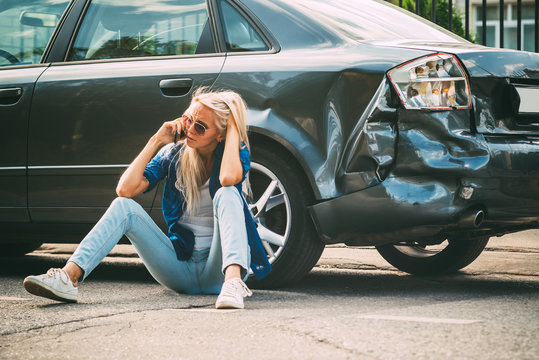 girl sits on the road, near the broken car and calls on the phone, calling for help.