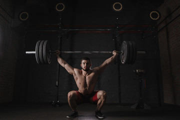 Crossfit athlete lifting heavy barbell overhead at the gym. Practicing powerlifting.