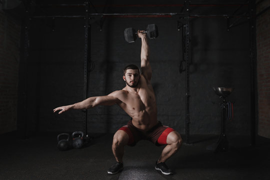 Crossfit athlete doing overhead dumbbell squats at the gym. Handsome man doing functional training. Practicing workout