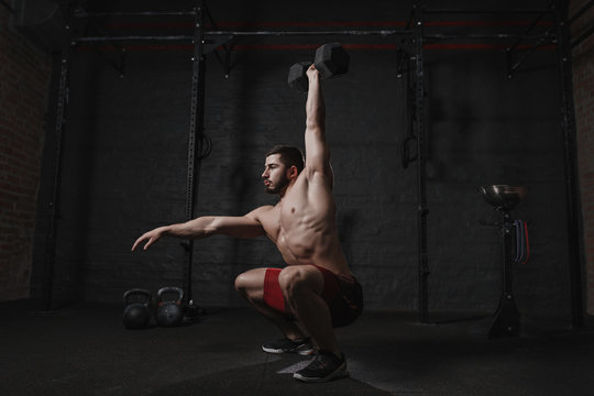 Crossfit athlete exercising at the gym doing overhead dumbbell squats.