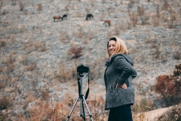 Happy woman - photographer taking pictures of horses in the wild
