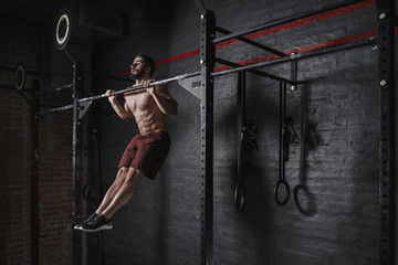 Crossfit athlete doing pull-ups at the gym. Practicing calisthenics. Handsome man doing functional training. Wall mural