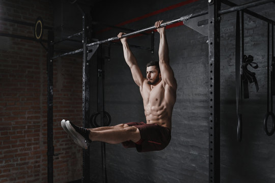 Crossfit athlete doing abs exercise on horizontal bar at the gym. Handsome man doing functional training workout. Practicing calisthenics.