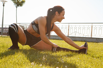 Side view of healthy sportswoman in top, shorts, leggings and sneakers stretching legs in morning outdoor. Beautiful girl with fit slim body warming up before run. Concept of sport and fitness.