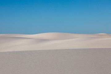 A blue sky overhead the white gypsum sand dunes at White Sands National monument, New Mexico