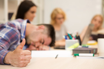 Sleeping boy gesturing thumb up, while group of student, studying at blurred background.