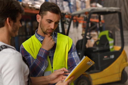 Concentrated workers of warehouse discussing something and looking at yellow clipboard. Serious manager wearing in reflective waistcoat thinking and holding hand near chin.