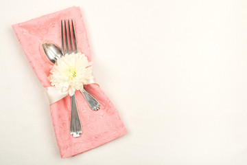Pretty Table Setting with Peachy Pink Cloth Napkin with fork, spoon, and flower on off white tablecloth