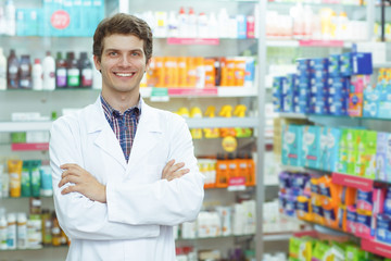 Front view of good looking pharmacist standing in drugstore. Handsome consultant smiling, looking at camera and posing. Background of shelves with medications.