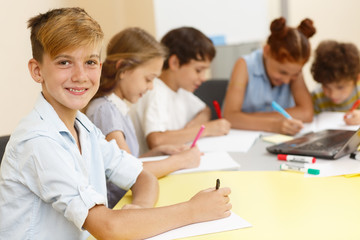 Stylish student of modern school in process of learning new material with classmates on background. Smiling  schoolboy sitting at table, writing in copybook, looking at camera and posing.