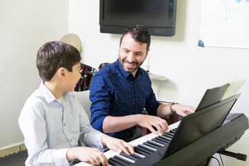Boy Learning To Play Piano From Smiling Instructor