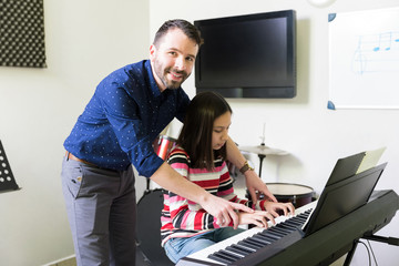 Smiling Tutor Assisting Girl In Playing Electric Piano
