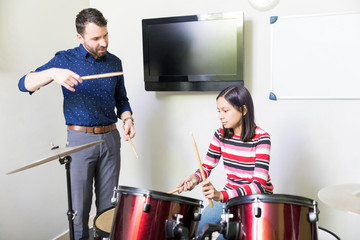 Teacher Giving Drumming Lessons To Girl In Class