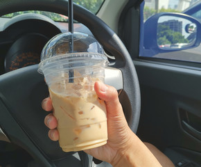 Close up image of hand holding a mug of ice cappuccino inside the car. Selctive focus, shallow dof.
