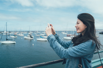 side view of young asian woman tourist taking photo of yacht with smart phone in front seat in Old Fisherman's Wharf monterey. smiling lady traveler holding cellphone standing on beach bay near boats