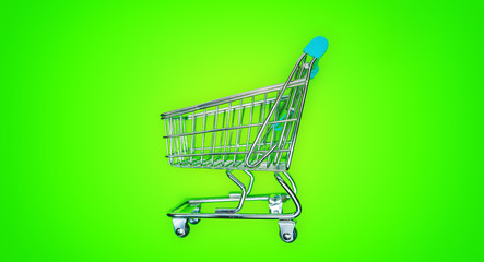 Miniature shopping cart isolated on green