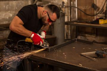 Handsome man engaging in manual labor and grinder metal angle grinder.