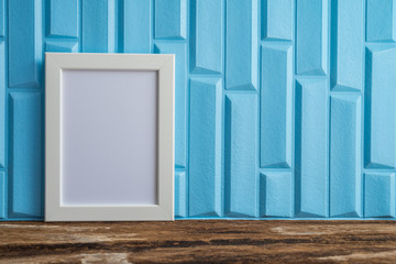 White photo frame on old wooden table over blue wallpaper background