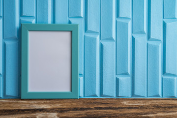 Blue photo frame on old wooden table over blue wallpaper background