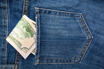 Paper banknotes 50 us dollars in the back pocket of blue jeans. Denim backgrounds.
