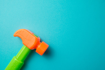 Flat lay of hammer plastic toy on blue background with copy space. Playing with toys can be an enjoyable means of training young children for life in society.