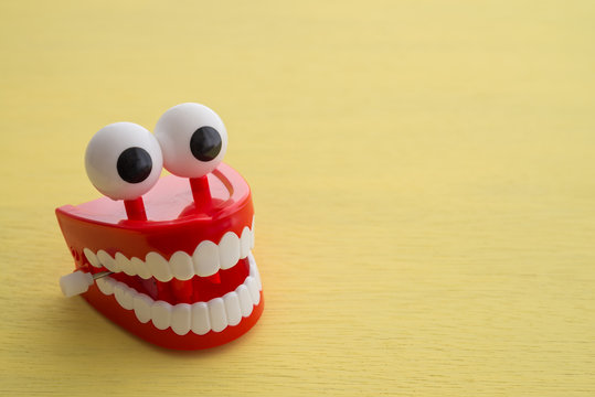 Chattering teeth toy wind up moving on yellow background. Funny, comedy, relax time concept