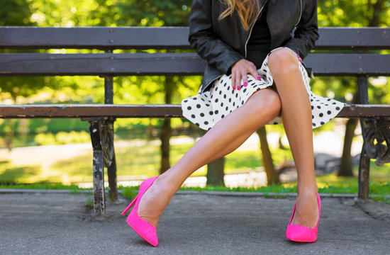 Fashionable woman with beautiful legs sitting on bench in park